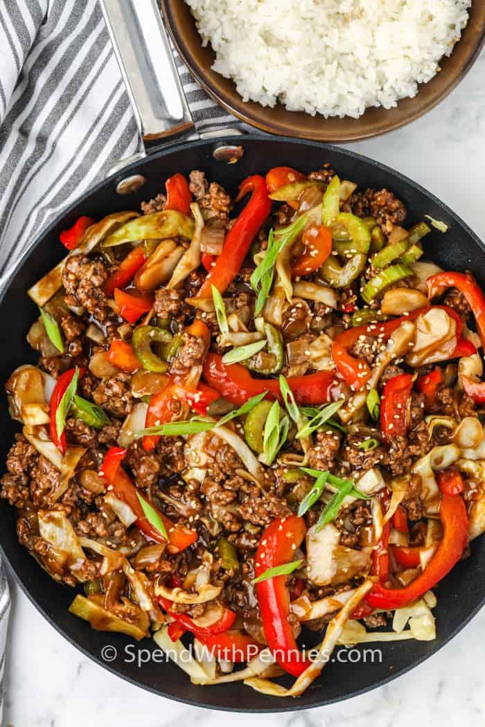 Vista superior del salteado de carne molida cocida en la sartén con un lado de arroz